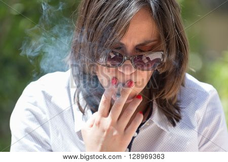 Close-up of adult brunette in sunglasses smoking cigarette while looking down