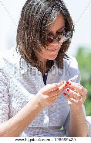 Close-up of brunette in sunglasses rolling handmade cigarette