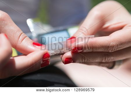 Close-up of woman rolling joint in sunlight