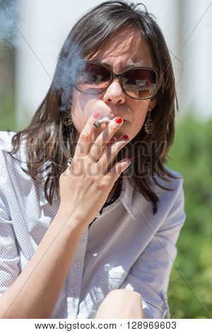 Young woman brunette smoking joint in sunlight
