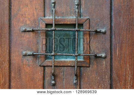 Small square window with grate in old style wooden door confinement concept