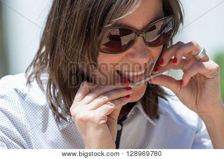 Close-up of smiling brunette in sunglasses making cigarette
