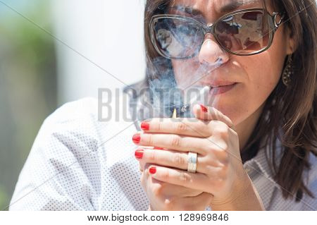 Close-up of woman in sunglasses lights up the cigarette