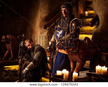 Medieval knights in ancient castle interior.