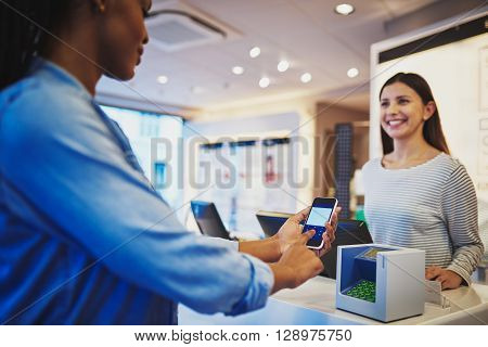 Woman Watching Customer Pay At Register With Phone