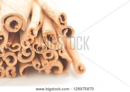 Artistic view of Raw Organic Cinnamon sticks (Cinnamomum verum) isolated on white background.