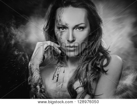 Black and white portrait of beautiful woman on smoked background.