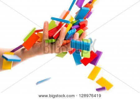 Falling colorful domino in air onto a hand