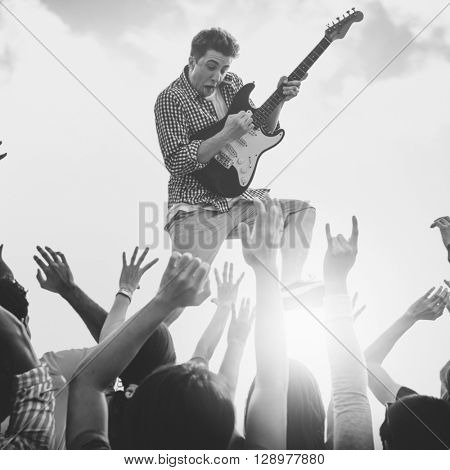 Young Man with a Guitar Performing on an Ecstatic Crowds