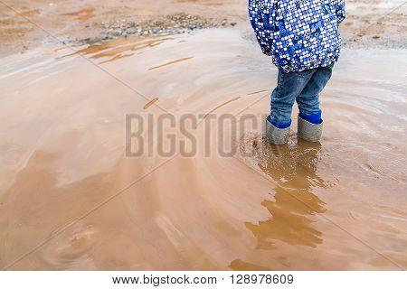 Child wearing rain boots jumping into a puddle. Close up