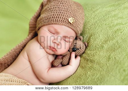 Peaceful sleep of a newborn baby with a favorite toy,happy kid in a knitted brown hat, sleeping sweetly on a soft green bed,putting his hand under his cheek and hugging toy brown bear
