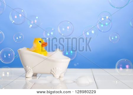 Little rubber duck taking a bath with floating soap bubbles