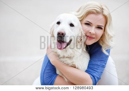 Young beautiful woman with curly blonde hair and brown eyes wearing a blue shirt and white jeans,spends time on the football field in the summer, playing with your favorite dog breed Golden Retriever