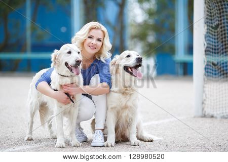 Young beautiful woman with curly blonde hair and brown eyes wearing a blue shirt and white jeans,spends time on the football field in the summer with two dogs of breed Golden Retriever
