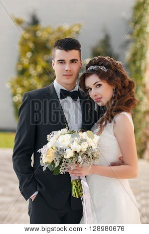 Loving couple, the groom is the brunette with short hair, wearing a dark suit and the bride a brunette with long curly hair in white wedding dress,beautiful tiara and earrings in their ears,standing with a bouquet of flowers embracing outdoors