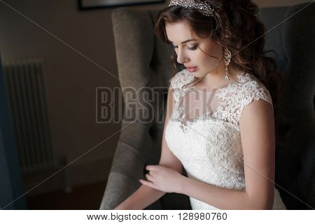Beautiful young woman with brown eyes,professional makeup, brunette with beautiful wedding hairstyle and tiara, ears expensive earrings, dressed in a white wedding dress sitting on the armchair in the hotel room