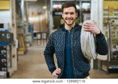 Smiling Young Handyman With A Roll Of Cable