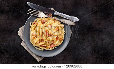 Delicious pasta carbonara on a black background
