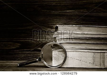 black and white photo. a pile of old books and magnifier on wooden background. the concept of the research the study. with space for text