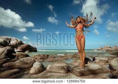 Young adult  girl on tropical beach. Flying Dreadlocks hair