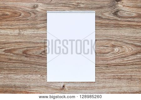 Mockup of open album with blank white page on wooden background. Vertical orientation, top view.
