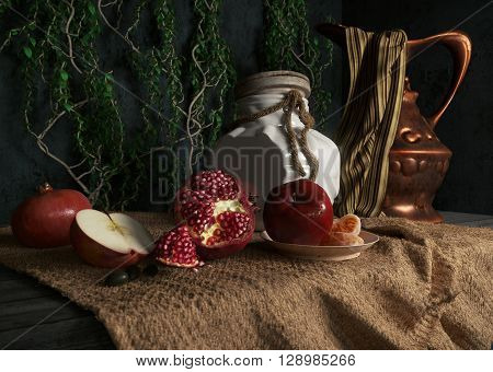 jar, rop, apples,pomegranate,plant and orange on canvas drapery conceptual