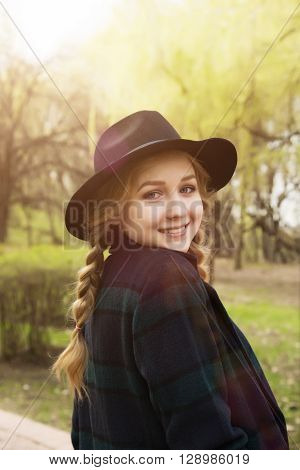 Pretty young girl in hat outdoors sunny day