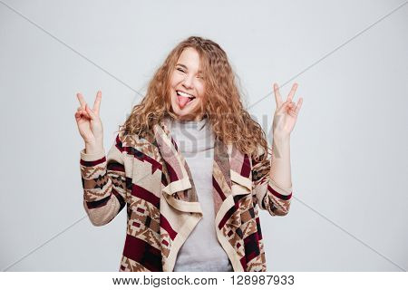 Funny woman showing tongue at camera isolated on a white background