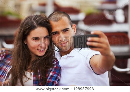 Happy couple at the bar making selfies