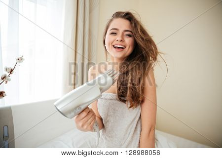 Laughing woman in towel dries hair with hairdryer on the bed at home