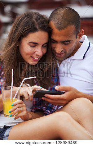Couple looking to a smart phone at the bar