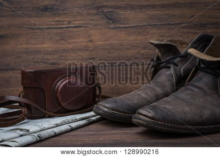 Old Worn Out Brown Leather Shoes With Camera And Newspaper Over The Dark Background