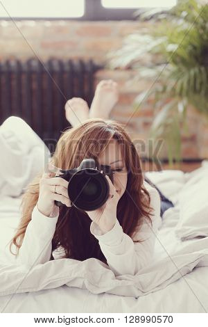 Beautiful woman in a bed with camera