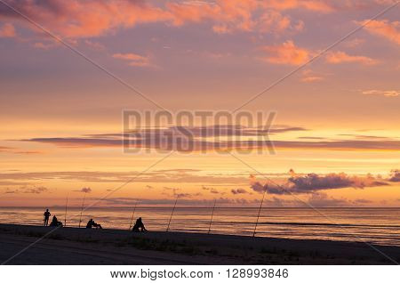 Fishers At Dramatic Sunset With Heavy Clouds At The Ocean