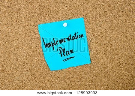 Implementation Plan Written On Blue Paper Note
