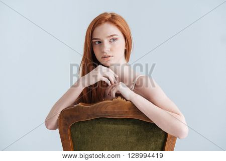 Pensive redhead woman sitting on the chair and looking away isolated on a white background