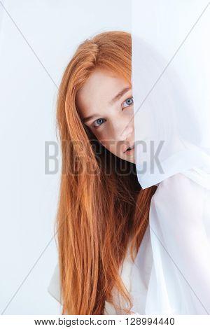 Cute redhead woman peeking from curtain