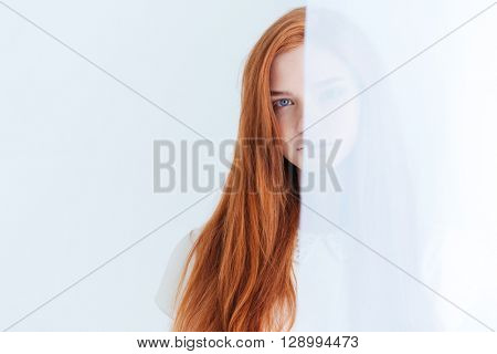 Charming redhead woman peeking from curtain