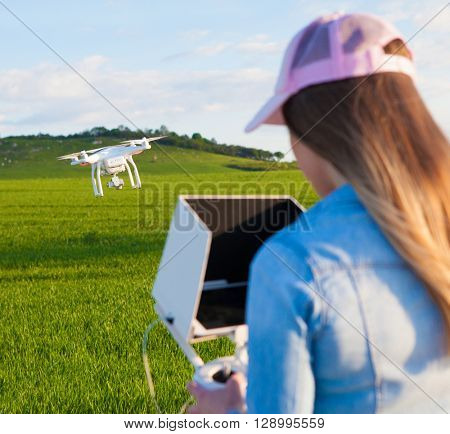 Young woman holding radio controller with tablet and sun shade flying drone uav over a field. Aerial video and photography maker. Hovering aircraft in the background.