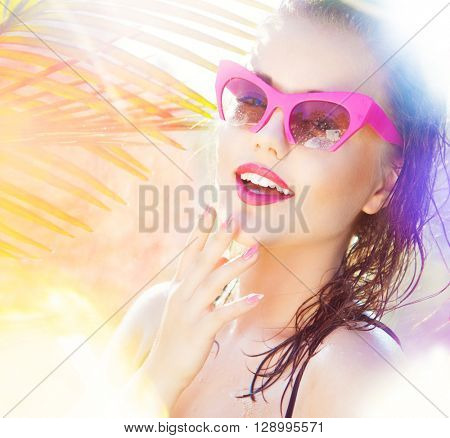 Colorful summer portrait of happy young attractive woman wearing wet sunglasses. wet hair beauty and