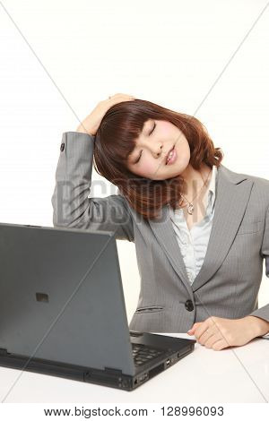 portrait of young businesswoman doing self neck stretch on white background
