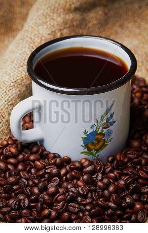Metal mug on grains on grains and sackcloth