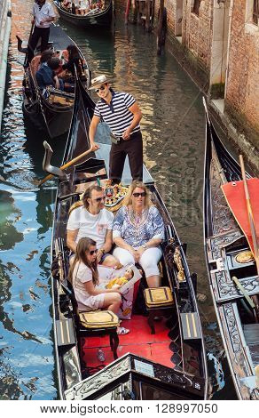 VENICE ITALY - MAY 27 2015: Parents and young girl sailing in gondola in Venice Italy. Gondolier is smiling at camera.