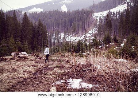 Woman tourist witnessing a desolated landscape of forests being cut down