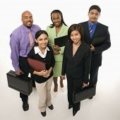 Portrait of multi-ethnic business group standing holding briefcases and looking at viewer.