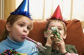 Caucasian children looking bored wearing party hats and blowing noisemakers.
