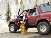 Woman with dog sitting with dirt splattered SUV automobile in snowy rural setting.