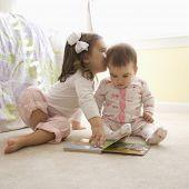 Caucasian Mädchen Kinder sitzen Erdgeschoss Schlafzimmer Blick in Buch. [3,5 Jahre und 8 Monate alt]