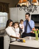 Caucasian mother and father in kitchen busy with children and cellphone.