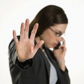 Caucasian mid adult professional business woman talking on cell phone holding hand out to stop viewe